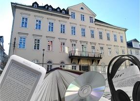 Außenansicht der Stadtbücherei als Collage mit Buch, E-Book-Reader, Kopfhörer, CD©Universitätsstadt Marburg